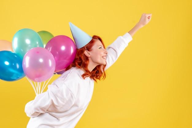 Mulher jovem, vista frontal, escondendo balões coloridos atrás das costas festa de ano novo emoção cor natal
