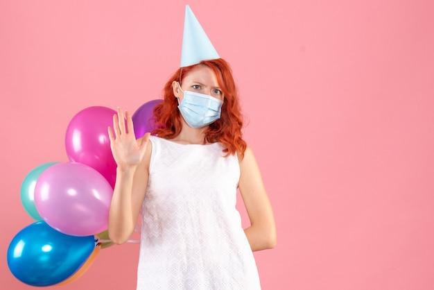 Mulher jovem, vista frontal, escondendo balões coloridos em máscara estéril em fundo rosa festa de ano novo cor de natal