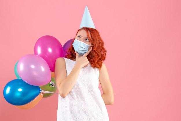 Mulher jovem, vista frontal, escondendo balões coloridos em máscara estéril pensando no fundo rosa festa covid- natal cor de ano novo