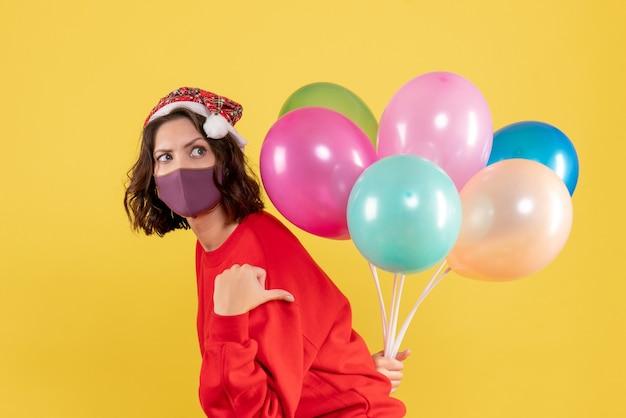 Mulher jovem, vista frontal, escondendo balões em estéril máscara cor férias emoção ano novo natal mulher