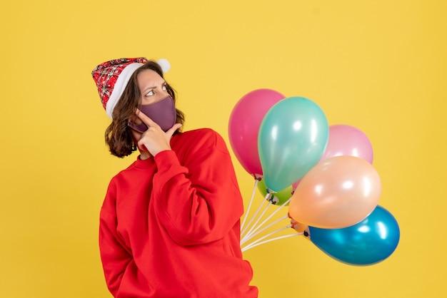 Mulher jovem, vista frontal, escondendo balões em máscara estéril natal mulher feriados cor emoção ano novo