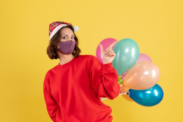 Mulher jovem, vista frontal, escondendo balões em máscara estéril natal mulher férias cores emoção ano novo