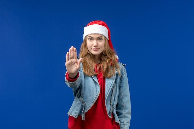 Mulher jovem, vista frontal, pedindo para parar no fundo azul emoção natal feriado cor
