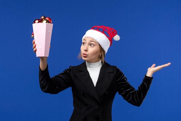 Mulher jovem, vista frontal, segurando os brinquedos da árvore no fundo azul, mulher, feriado de ano novo, azul