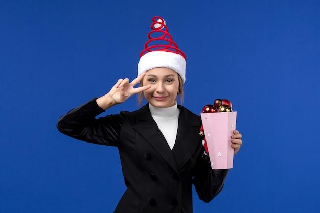 Mulher jovem, vista frontal, sorrindo com árvore de brinquedos na parede azul, cor de emoção do feriado de ano novo