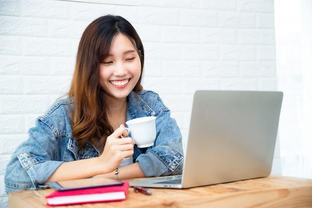 Mulher jovem, xícara café segurando, e, uso, laptop, em, escritório