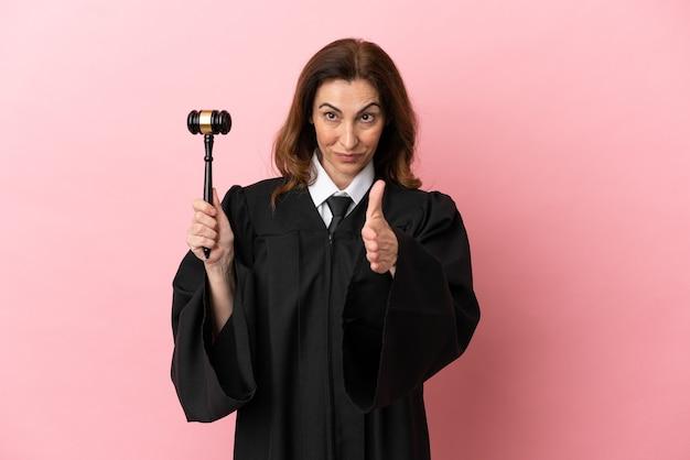 Mulher juíza de meia-idade isolada em fundo rosa apertando as mãos para fechar um bom negócio