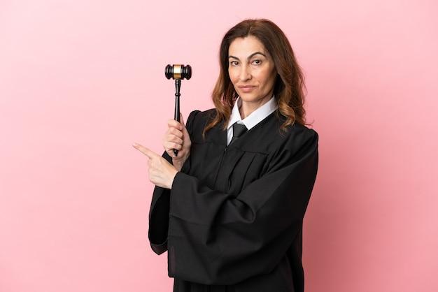 Mulher juíza de meia-idade isolada em fundo rosa apontando para trás