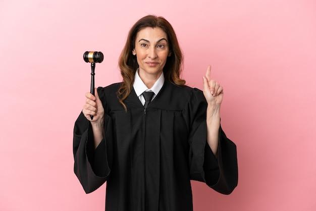 Mulher juíza de meia-idade isolada em fundo rosa apontando uma ótima ideia