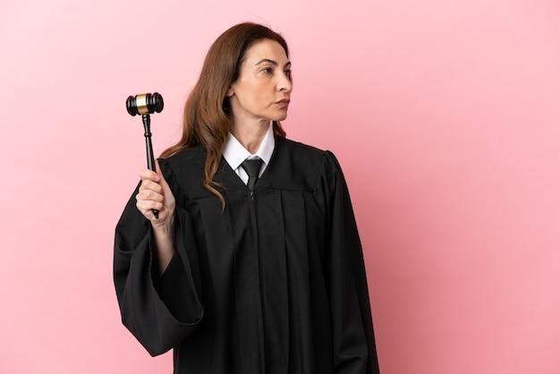 Mulher juíza de meia-idade isolada em fundo rosa olhando para o lado