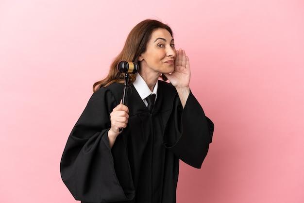 Mulher juíza de meia-idade isolada em um fundo rosa gritando com a boca bem aberta para o lado