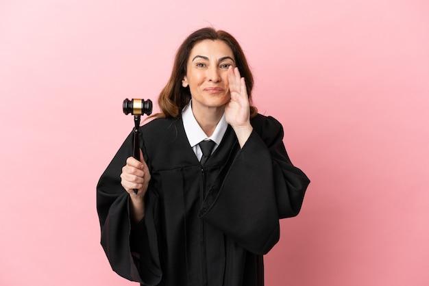 Mulher juíza de meia-idade isolada em um fundo rosa gritando com a boca bem aberta