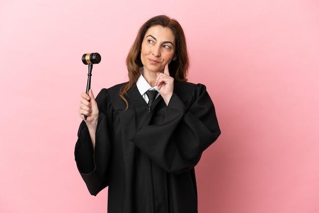 Mulher juíza de meia-idade isolada em um fundo rosa pensando em uma ideia enquanto olha para cima