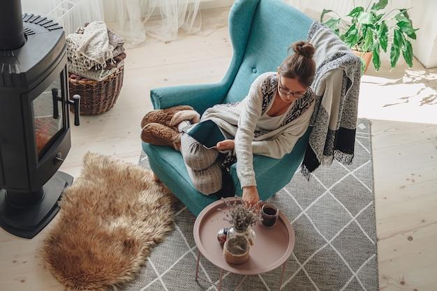 Mulher junto à lareira, sentada em uma poltrona aconchegante, com um cobertor quente, usando um tablet