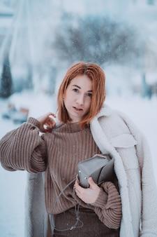 Mulher lá fora no dia frio de inverno a nevar