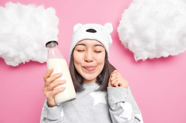 Mulher lambe os lábios fecha os olhos quer beber leite no café da manhã vestida com roupas confortáveis domésticas levanta a mão sente tentação isolada em rosa Foto gratuita