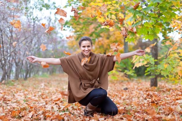 Mulher lança folhas de outono