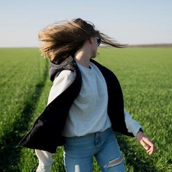 Mulher lançando a cabeça no campo