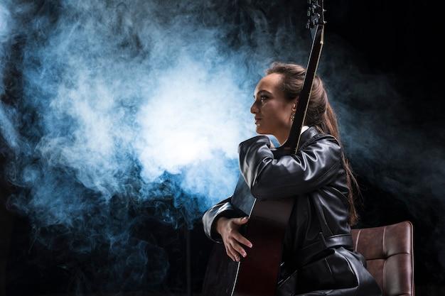 Mulher lateral, abraçando o violão e palco de fumaça