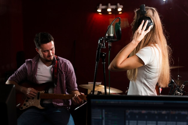 Mulher lateral cantando e cara sentado com um violão