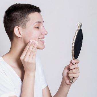 Mulher lateral, limpando o rosto enquanto olha no espelho