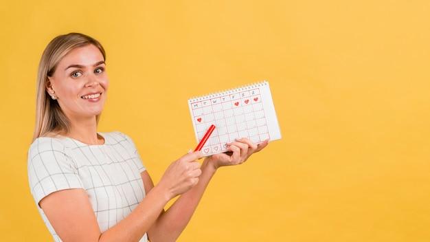 Mulher lateral mostrando seu calendário de menstruação