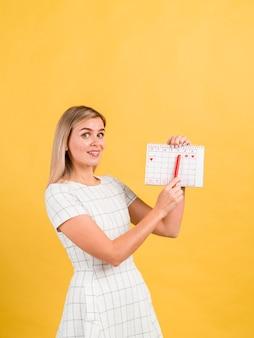 Mulher lateral mostrando seu calendário menstrual