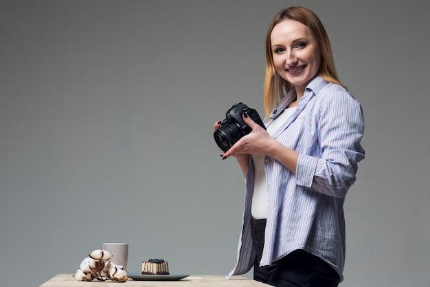 Mulher lateral, segurando uma câmera profissional em estúdio