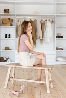 Mulher lateral, sentado na cadeira ao lado de vestir