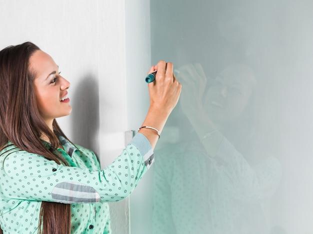Mulher lateralmente escrevendo estatísticas no quadro branco