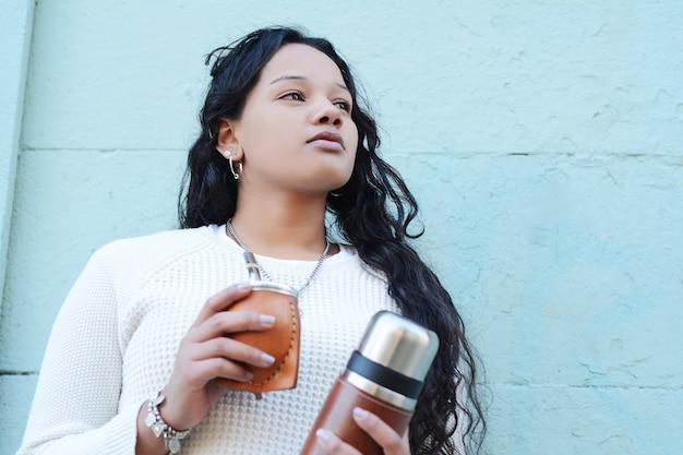 Mulher latin nova que bebe o chá tradicional do companheiro do yerba.
