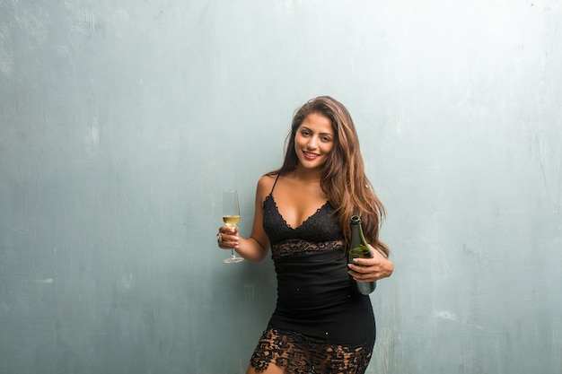 Mulher latin nova que comemora o ano novo ou um evento. animado e feliz, segurando uma garrafa de champanhe e uma xícara.