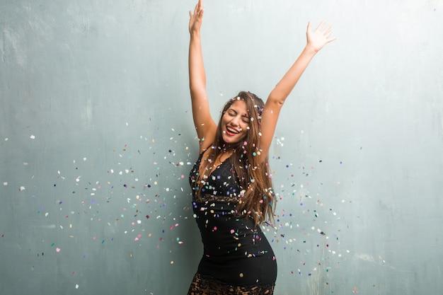 Mulher latin nova que comemora o ano novo ou um evento. muito feliz e animada, levantando os braços.