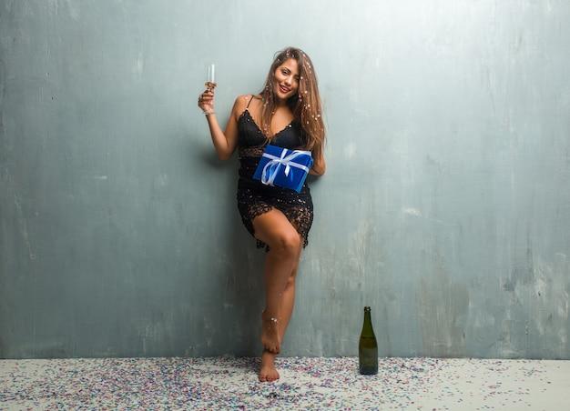 Mulher latin nova que comemora um ano novo ou um evento, bebendo o champanhe, com os pés descalços e prendendo um presente azul.