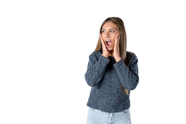 Mulher latina atraente com uma expressão chocada em um fundo branco puro. fotografia de estúdio.