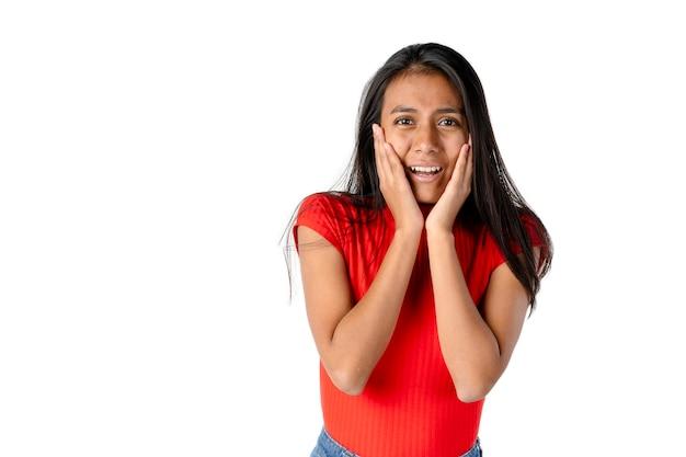 Mulher latina atraente de cabelos escuros com as mãos em concha no rosto e expressão de pânico em um fundo branco puro.