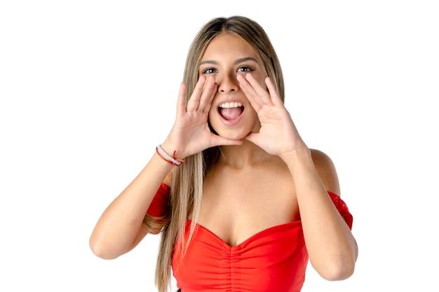Mulher latina atraente gritando com as mãos nas laterais da boca em um fundo branco puro.