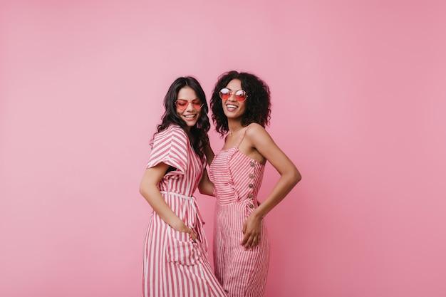 Mulher latina bem torneada em roupa listrada, posando com uma amiga africana. a foto interna de duas mulheres atraentes usa óculos de sol cor de rosa da moda.