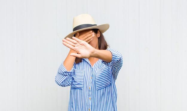 Mulher latina cobrindo o rosto com a mão e colocando a outra mão na frente para parar a câmera, recusando fotos ou imagens