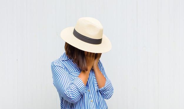 Mulher latina cobrindo os olhos com as mãos com uma expressão triste e frustrada de desespero, chorando, vista lateral