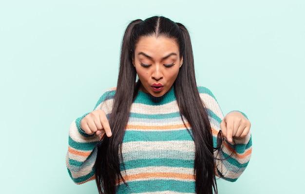 Mulher latina com a boca aberta apontando para baixo com as duas mãos, parecendo chocada, espantada e surpresa