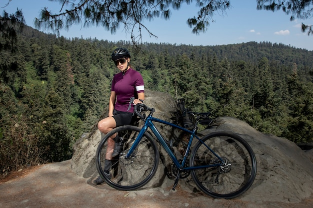 Mulher latina com bicicleta descansando na floresta com uma paisagem de árvores ao fundo