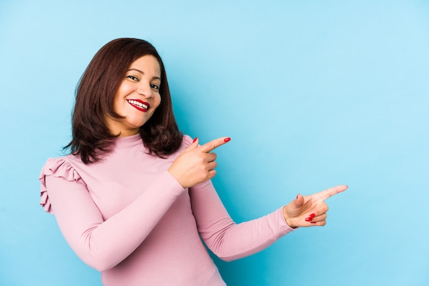 Mulher latina de meia-idade animado apontando com o dedo indicador fora.