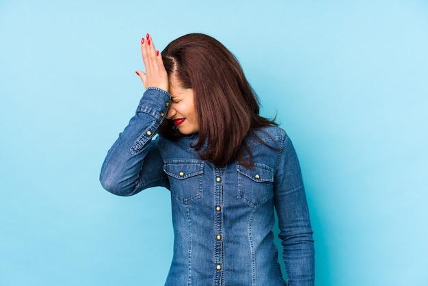 Mulher latina de meia-idade isolada em azul, esquecendo algo, batendo na testa com a palma da mão e fechando os olhos.