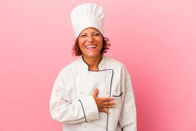 Mulher latina de meia-idade isolada em fundo rosa ri alto, mantendo a mão no peito.