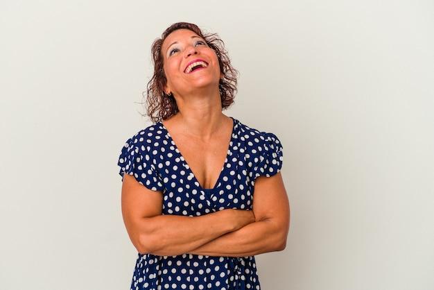 Mulher latina de meia-idade isolada em um fundo branco, sonhando em alcançar objetivos e propósitos