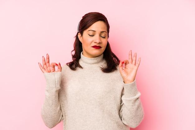 Mulher latina de meia-idade isolada em um fundo rosa relaxa após um árduo dia de trabalho, ela está realizando ioga.