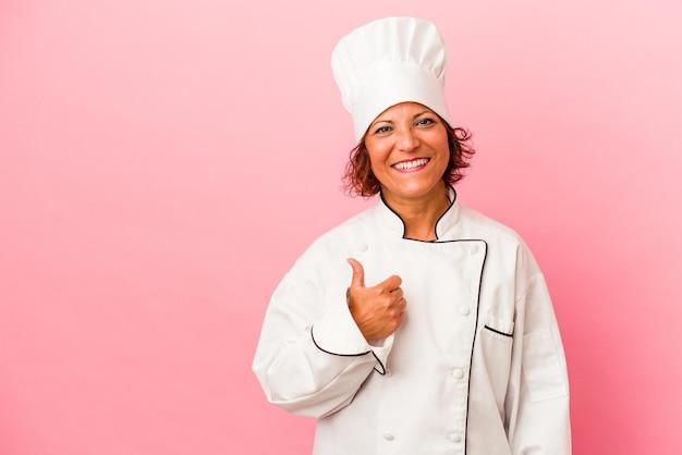 Mulher latina de meia-idade isolada em um fundo rosa sorrindo e levantando o polegar