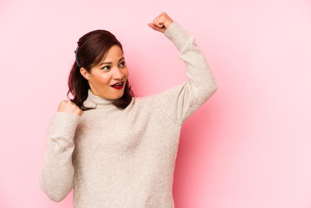 Mulher latina de meia-idade isolada em uma parede rosa levantando o punho após uma vitória, conceito vencedor