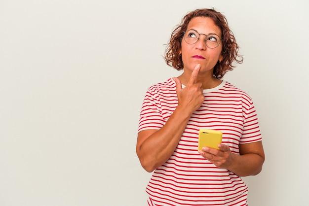 Mulher latina de meia-idade isolada no fundo branco, olhando de soslaio com expressão duvidosa e cética.